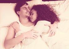 Jeunes conjoints étreignant comme dormant dans le lit Images stock