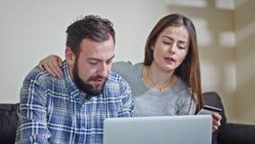 Jeunes couples à la maison achetant sur l'Internet Photo libre de droits