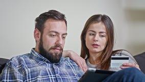 Jeunes couples à la maison achetant sur l'Internet Image stock