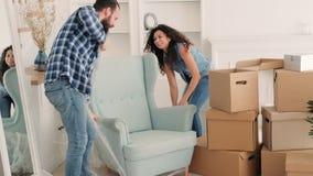 Jeunes couples à la maison en mouvement ayant le déballage d'amusement clips vidéos