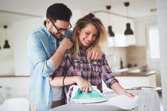 Jeunes couples à la maison faisant des corvées et repasser de hosehold Image stock