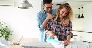 Jeunes couples à la maison faisant des corvées et repasser de hosehold Photo libre de droits