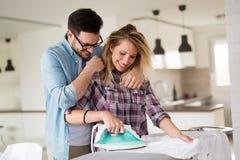 Jeunes couples à la maison faisant des corvées et repasser de hosehold Photographie stock libre de droits