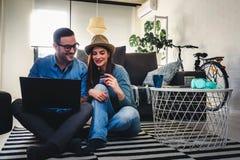 Jeunes couples à la maison faisant des emplettes en ligne photos stock