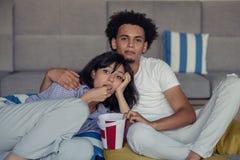 Jeunes couples à la maison observant un film avec le maïs éclaté photographie stock libre de droits