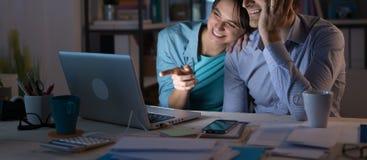 Jeunes couples à la maison utilisant un ordinateur Image stock
