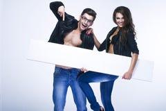 Jeunes couples à la mode tenant le conseil blanc Image stock