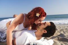 Jeunes couples à la plage environ à embrasser photo stock
