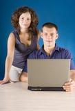 Jeunes couples à la table avec l'ordinateur portatif Photographie stock