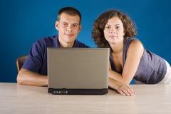 Jeunes couples à la table avec l'ordinateur portatif Photographie stock libre de droits