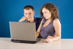 Jeunes couples à la table avec l'ordinateur portatif Images libres de droits