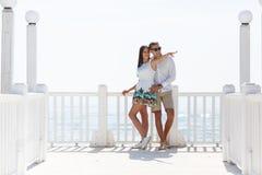 Jeunes couples à une station de vacances près de la mer La fille indique la distance Images libres de droits