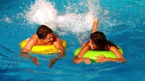 Jeunes couples éclaboussant et ayant l'amusement dans la piscine sur les anneaux gonflables banque de vidéos