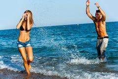 Jeunes couples éclaboussant l'eau sur le côté de mer. Photos libres de droits