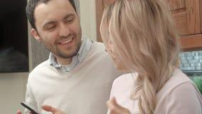 Jeunes couples écoutant la musique par l'intermédiaire du smartphone, parlant dans la cuisine Photos stock