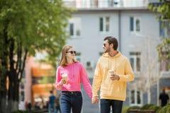 Jeunes couples élégants dans des lunettes de soleil avec des tasses de café tenant des mains et la marche Photo stock