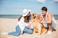 Jeunes couples élégants dans jouer se reposant d'amour avec le chien Image stock