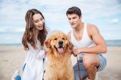 Jeunes couples élégants dans jouer se reposant d'amour avec le chien Photos stock
