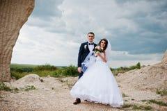 Jeunes couples élégants de mariage contre la carrière arénacée au ciel nuageux Image stock