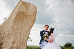 Jeunes couples élégants de mariage contre la carrière arénacée au ciel nuageux Photo libre de droits