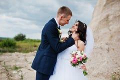 Jeunes couples élégants de mariage contre la carrière arénacée au ciel nuageux Photographie stock