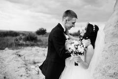 Jeunes couples élégants de mariage contre la carrière arénacée au ciel nuageux Photos libres de droits