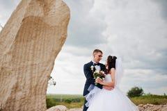 Jeunes couples élégants de mariage contre la carrière arénacée au ciel nuageux Photos stock