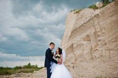 Jeunes couples élégants de mariage contre la carrière arénacée au ciel nuageux Images stock