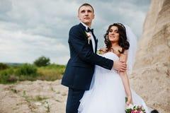 Jeunes couples élégants de mariage contre la carrière arénacée au ciel nuageux Images libres de droits