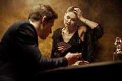 Jeunes couples élégants jouant le tisonnier dans le casino Photographie stock