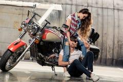 Jeunes couples élégants posant avec la motocyclette dans le garage Photos stock