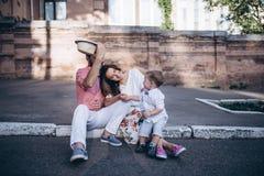 Jeunes couples élégants se reposant sur le trottoir dans la vieille ville dans la ville Garçon beau heureux avec ses parents Photo stock
