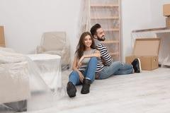 Jeunes couples étant fatigués après préparation pour la relocalisation à la nouvelle maison images stock