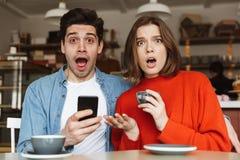 Jeunes couples étonnés se reposant au café Photo stock