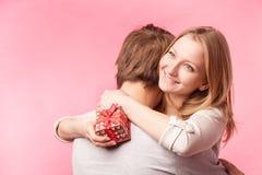 Jeunes couples étreignant avec le présent enveloppé Photos stock