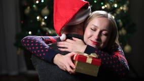Jeunes couples étreignant avec le présent enveloppé de Noël banque de vidéos