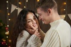 Jeunes couples étreignant dans l'intérieur en bois foncé avec des lumières Soirée et concept romantiques d'amour Vacances d'an ne Photo libre de droits
