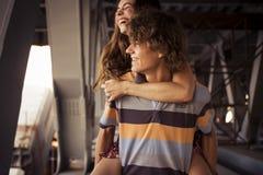 Jeunes couples étreignant dans la lumière du jour d'été sur un construc de pont Photographie stock libre de droits