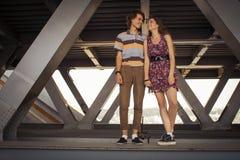 Jeunes couples étreignant dans la lumière du jour d'été sur un construc de pont Photo libre de droits