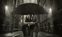 Jeunes couples étreignant sous la pluie Photos libres de droits