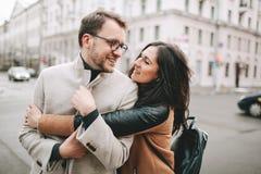 Jeunes couples étreignant sur la rue de ville en hiver Image stock