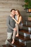Jeunes couples étreignant tout en se reposant sur l'escalier Image libre de droits