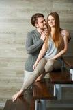 Jeunes couples étreignant tout en se reposant sur l'escalier Photo stock
