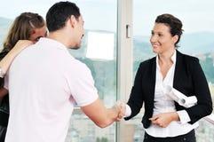Jeunes couples achetant la maison neuve avec l'agent immobilier Image stock