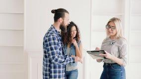 Jeunes couples achetant le nouvel appartement propriétaires heureux banque de vidéos