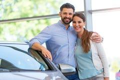 Jeunes couples achetant une voiture photographie stock
