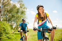 Jeunes couples ACTIFS faisant du vélo sur un chemin forestier en montagne sur un spr photo libre de droits