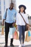 Jeunes couples actifs semblant satisfaits avec leurs achats Photographie stock libre de droits