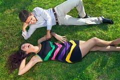 Jeunes couples adolescents détendant sur l'herbe Photos stock