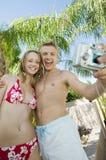 Jeunes couples adoptant à photo de lui-même la position d'angle faible Image stock